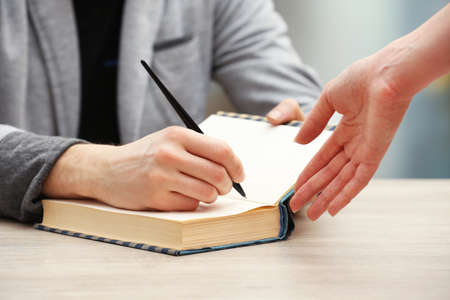 Foto de Author signing autograph in own book at wooden table on light blurred background - Imagen libre de derechos