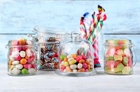 Photo for Multicolor candies in glass jars on color wooden background - Royalty Free Image