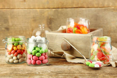 Photo for Multicolor candies in glass jars on wooden background - Royalty Free Image