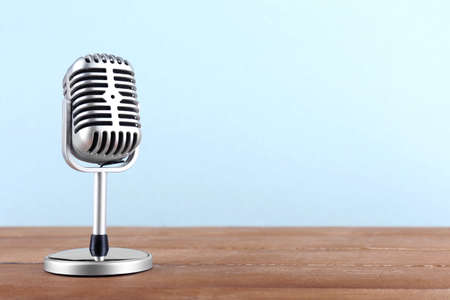 Photo for Retro microphone on wooden table on light background - Royalty Free Image