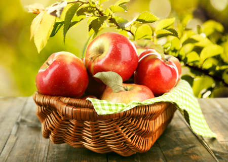 Wicker basket of red apples with napkin on nature background