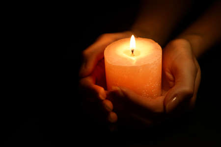 Foto de Candle in female hands on black background - Imagen libre de derechos