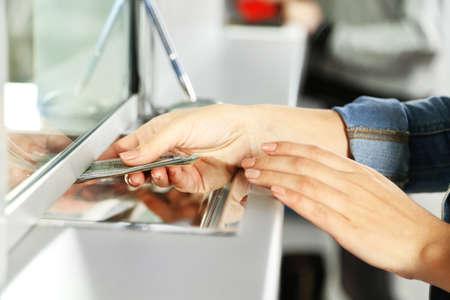 Foto de Female hand with money in cash department window. Currency exchange concept - Imagen libre de derechos