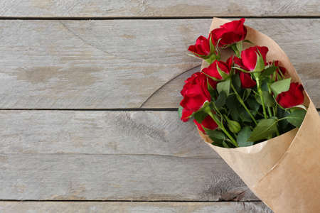 Photo pour Red roses wrapped in paper on wooden table background - image libre de droit