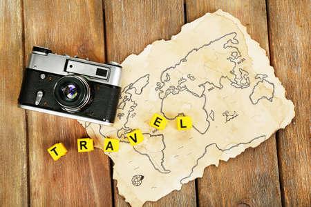Foto de Retro camera on world map with word Travel on wooden table background - Imagen libre de derechos