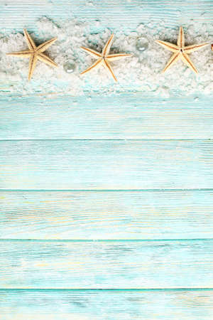 Foto de Sea stars on sea salt on wooden background - Imagen libre de derechos