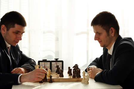 Photo for Two handsome businessmen playing chess in office - Royalty Free Image