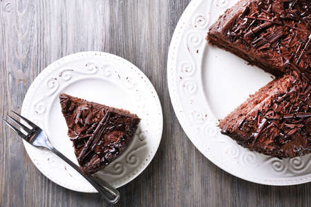 Photo pour Sliced tasty chocolate cake on wooden table  - image libre de droit