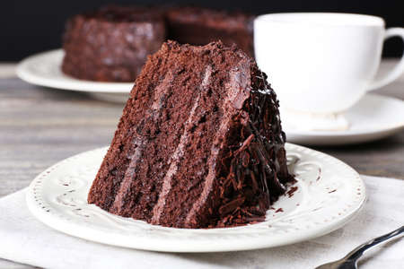 Foto de Delicious chocolate cake in white plate on wooden table , closeup - Imagen libre de derechos