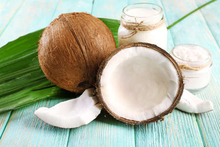 Photo for Fresh coconut oil in glassware and green leaf on color wooden table background - Royalty Free Image