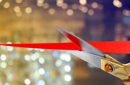 Photo pour Scissors cutting red ribbon - image libre de droit
