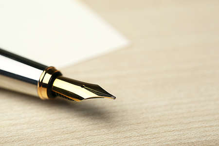 Photo for Fountain pen on white sheet of paper and wooden table background - Royalty Free Image