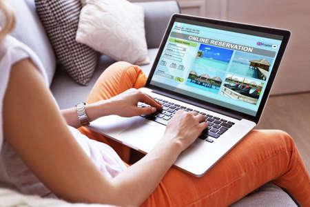 Foto de Woman using laptop to book hotel online - Imagen libre de derechos