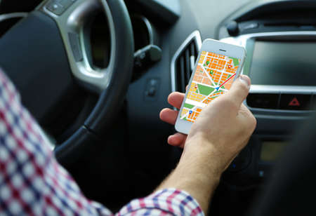 Photo pour Man sitting in the car and holding smart phone with map gps navigation application - image libre de droit