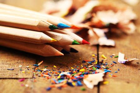 Photo pour Wooden colorful pencils with sharpening shavings, on wooden table - image libre de droit