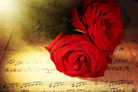 Photo pour Beautiful red roses on music sheets, closeup - image libre de droit