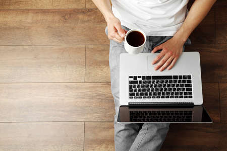 Photo for Young man sitting on floor with laptop and cup of coffee in room - Royalty Free Image