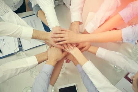 Photo pour United hands of business team on workspace background top view - image libre de droit