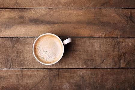 Photo pour Cup of coffee on wooden table, top view - image libre de droit