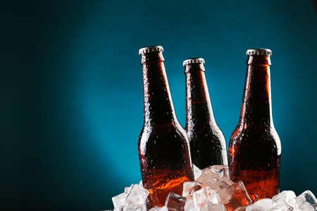 Foto de Glass bottles of beer in ice cubes on color background - Imagen libre de derechos
