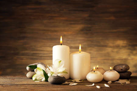 Photo pour Beautiful composition with candles and spa stones on wooden background - image libre de droit