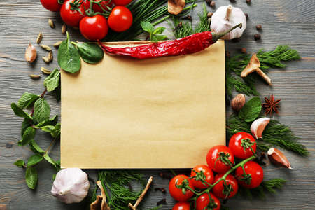 Foto per Open recipe book with fresh herbs, tomatoes and spices on wooden background - Immagine Royalty Free