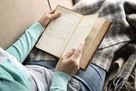 Photo pour Young woman reading book, close-up, on home interior background - image libre de droit