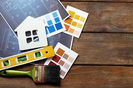 Photo pour Color samples, decorative house, gloves and paintbrushes on wooden table background - image libre de droit