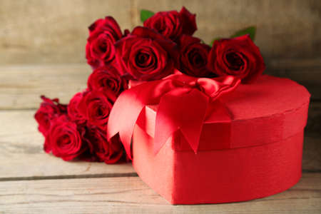 Foto de Heart shaped Valentines Day gift box with red roses on old wooden table - Imagen libre de derechos