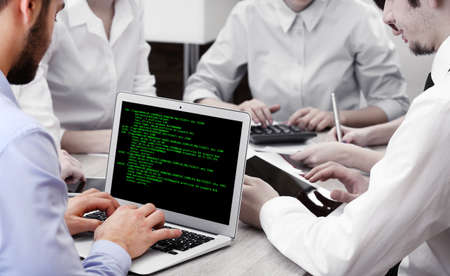 Foto de Man using laptop, writing programming code on laptop - Imagen libre de derechos