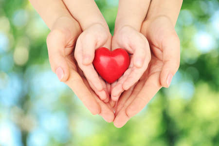 Foto de Heart in child and mother hands on green nature background. Concept of taking care, protection, helping and assistance - Imagen libre de derechos
