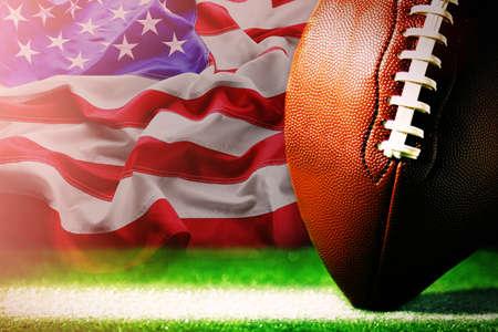 Foto de American football on green grass, on flag of United States of America background - Imagen libre de derechos