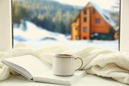 Foto de Cup of hot drink and book on the windowsill in winter landscape background - Imagen libre de derechos