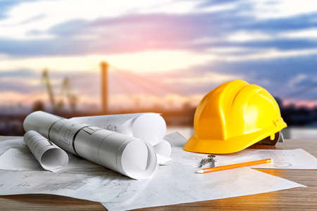 Foto de Construction blueprints with tools and helmet on sky background - Imagen libre de derechos