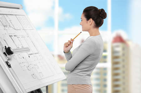 Photo for Young female engineer working with project on drawing board in office - Royalty Free Image