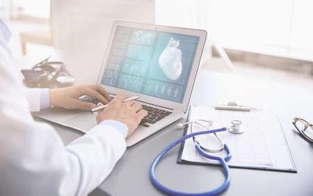 Foto de Cardiologist working with laptop at office. Health care concept. - Imagen libre de derechos