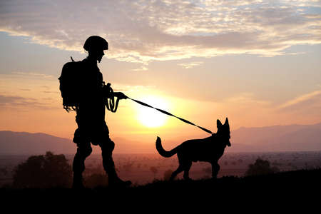 Foto de Silhouettes of soldier and dog on sunset background. Military service concept. - Imagen libre de derechos