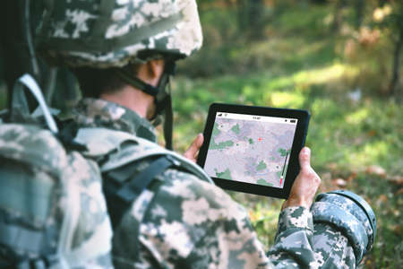 Foto de Soldier using map on tablet for orientation at forest - Imagen libre de derechos