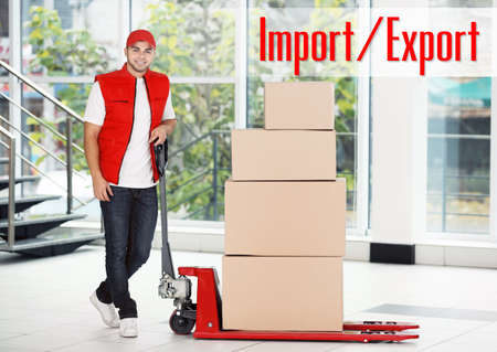 Foto per Delivery man in uniform with hand palette truck and cardboard boxes at storehouse. Text IMPORT/EXPORT on background. Wholesale and logistics concept. - Immagine Royalty Free