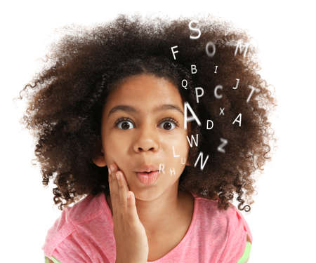 Foto de African-American little girl with book and alphabet letters on white background. Speech therapy concept - Imagen libre de derechos
