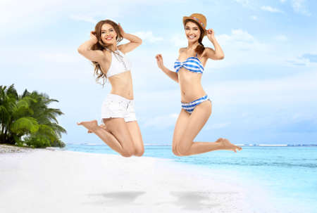 Photo for Two happy girls enjoying summer and jumping on the beach - Royalty Free Image