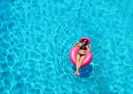 Photo for Beautiful young woman with inflatable donut in swimming pool - Royalty Free Image