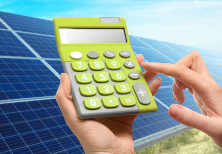 Photo pour Woman holding calculator and solar panels on background. Reduction of expenses on electricity - image libre de droit