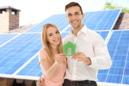 Photo pour Young couple holding figure of house and solar panels on background - image libre de droit