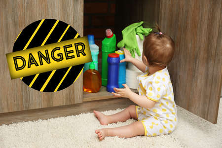 Photo pour Baby playing with detergents in kitchen - image libre de droit