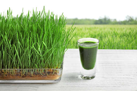 Photo pour Glass of juice and wheat grass field  on background - image libre de droit