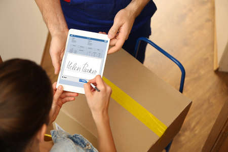 Foto für Woman appending signature after receiving parcel from courier at home - Lizenzfreies Bild