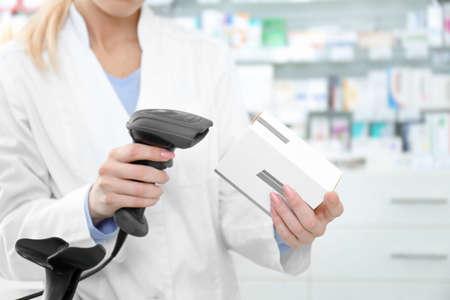 Foto de Female cashier scanning barcode on package at shop - Imagen libre de derechos