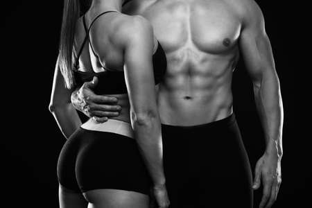 Foto de Young sporty couple posing on black background. Black and white photo - Imagen libre de derechos