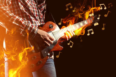 Photo for Young man playing electric guitar and fire surrounding instrument on dark background - Royalty Free Image